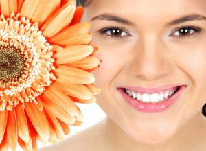 Woman smiling next to a giant orange flower